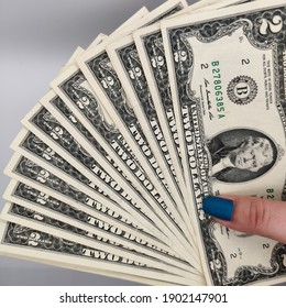 woman's hand holding a bunch of two dollar bills. rare collector US cash money