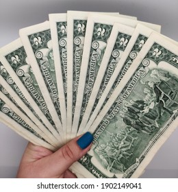 woman's hand holding a bunch of Us 2 dollar bills upside down, back of bills money cash