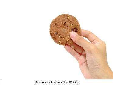 Woman's hand holding up a chocolate cookies.