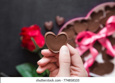 Woman's hand holding a chocolate heart. Cute gift from beloved. Red rose with chocolate box of heart shape with pink ribbon on the table. Enjoying sweets. Valentine's day and relationships concept.
