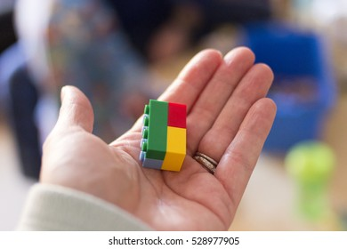 Woman's hand holding colorful plastic toy building blocks.