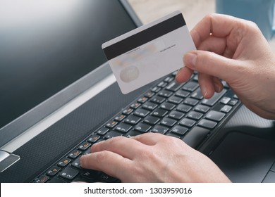 Woman's hand holding credit card over notebook and using it to pay online with it, concept of e-commers and online payment