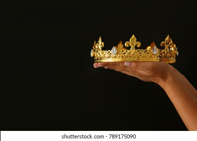 Woman's hand holding a crown for show victory or winning first place over black background