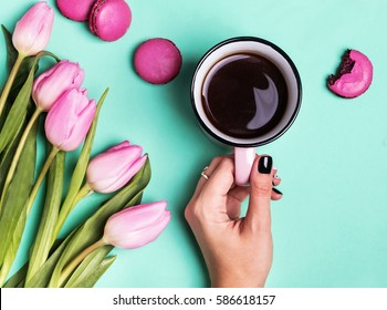 Woman's hand holding cup with coffee and pink tulips, top view.