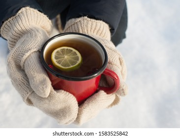 Woman's hand holding cup of tea with lemon on a cold day