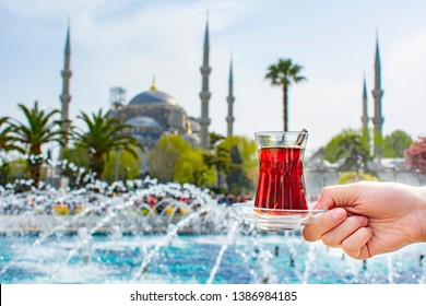 Woman's hand holding cup with Traditional turkish tea in front of Blue mosque (aka Sultanahmet Camii) in Istanbul, Turkey. Istanbul's main attractions.