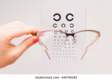 Woman's hand holding eyeglasses in front of page with Landolt C test. Japanese Vision Test