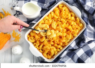 woman's hand is holding a fork with small portion of Mac and cheese or elbow pasta baked with cream and sharp cheddar cheese sauce in dish, authentic american recipe, view from above