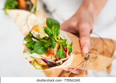 Woman's hand holding a fresh tortilla wrap tied round with brown paper and string. Gourmet conception.