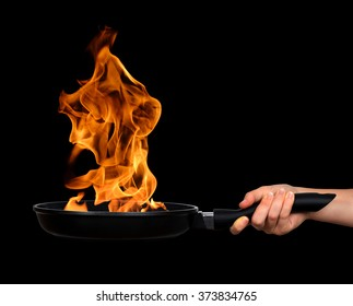 Woman's hand holding a frying pan with flames on black background