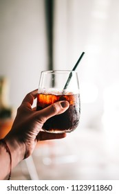 Woman's hand holding glass of black cold brew coffee with ice. Hipster coffee shop. Minimalism drink photography