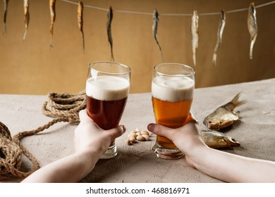 Woman's hand holding a glasses with beer