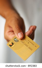 Woman's Hand Holding a Gold Credit Card