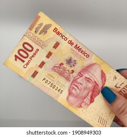 woman's hand holding a hundred Mexican peso bill money cash in hand