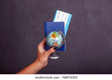 Womans hand holding international passport, airplane ticket and globe before grey isolated background