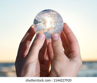 Woman's hand holding Lemurian Clear Quartz Sphere at the sunrise in front of the lake.