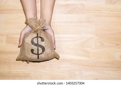 Woman's hand holding the money bag and has a dollar symbol and on wooden background, presented or as a basis for saving money on investments or saving money for use in need Or for the future. - image.