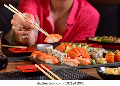 Woman's Hand holding a nigiri sushi on a restaurant table
