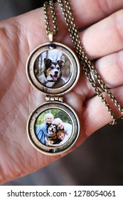 A woman's hand is holding an open gold antique locket and chain with pictures of children and a pet dog inside.
