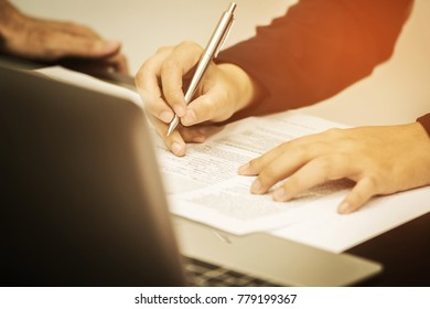 A woman's hand holding pen pointing on summary report chart and calculate finance in office.