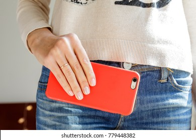 woman's hand holding the phone in the red case close up