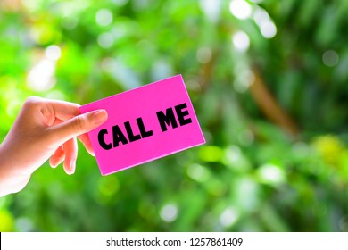 A woman's hand holding a pink color paper with a text written 'call me' on it. Green nature background.