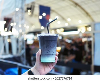 A woman's hand holding plastic glass of iced black cocao with mint; upper layer is black bitter cocao lower is pastel mint. Blur background with selective focus.