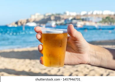 Woman's hand holding plastic glass of beer on sea beach.