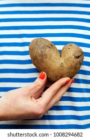 Woman's hand holding a potatoes in the form of heart  on the background of striped vest