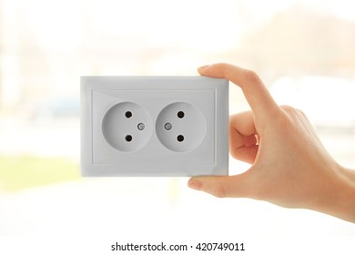Woman's hand holding power outlet