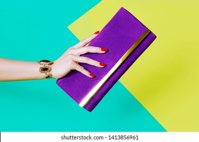 Woman's hand holding purple purse