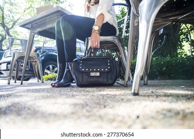 Woman's hand holding purse on ground with lens flare