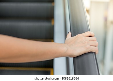 woman's hand is holding the rail of the escalator