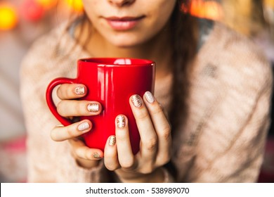 Woman's hand holding a red cup of coffee. With a beautiful winter manicure. Drink, fashion, morning
