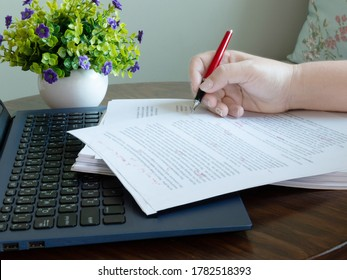 woman's hand holding red pen on pile of paperwork on table