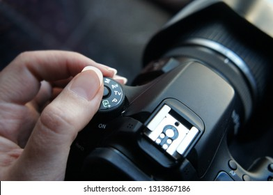 Woman's hand holding a reflex photo camera while adjusting dial mode close up
