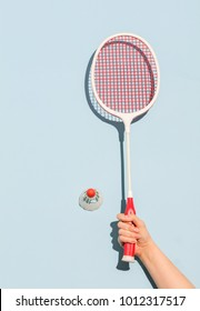 Woman's hand holding a retro badminton racket on pastel blue background. Sports and hobby.