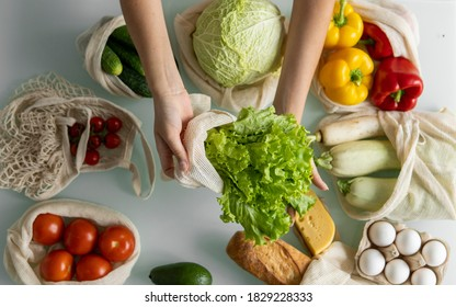 Woman's hand, holding a reusable grocery bag with vegetables on a kitchen at home and takes salad out. Zero waste and plastic free concept. Mesh cotton shopper with vegetables. Ecology.