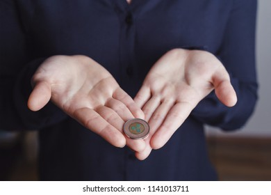 Woman's hand holding ripple coin