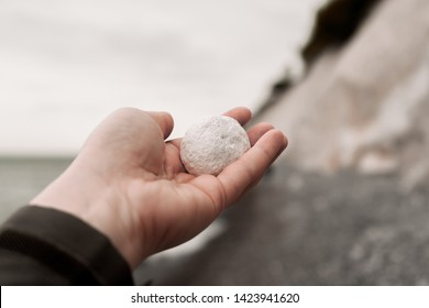 womans hand holding a round piece af chalk. Blurred background of Møns klint, the beach and the ocean. Grey and dark green colors. Moen cliffs, Denmark.