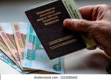 Woman's hand holding russian pension certificate, russian rubles in background. Russian translation - Ministry of Social Protection of Population of Russian Federation. Pension Certificate.