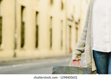 Woman's hand holding shopping bags, with fashionable clothes.