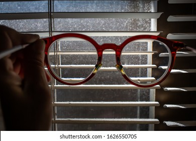 Woman's hand holding   shortsighted or nearsighted eyeglasses with Dust blinds inside a window, Dust and Dirty mosquito wire screen window, Light & Shadow shot, Close up shot, Selective focus