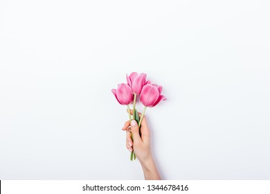 Woman's hand holding small bouquet of pink tulip flowers on white background with copy space for text.