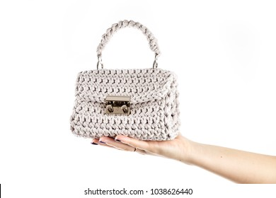 Woman's hand is holding a small crocheted cross body bag of beige color isolated on white background.
