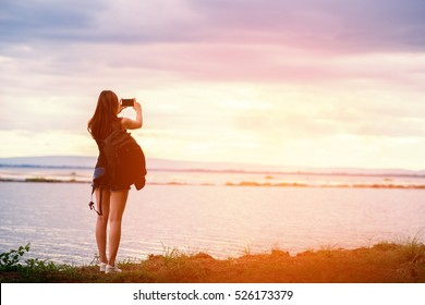 woman's hand holding smart phone, mobile, smart phone over blurred beautiful blue sea to take a photo of the sea