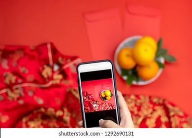 Woman's hand holding smartphone to captures Chinese new year oranges angpao pocket and qipao dresses