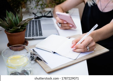 Woman's hand holding smartphone and making notes in notepad in cozy summer office with laptop