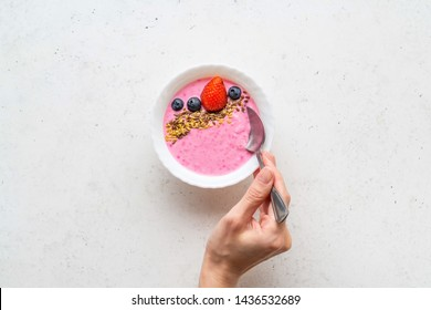Woman's hand holding spoon in the Smoothie bowl with fresh berries, golden and brown flax seeds. Healthy breakfast, fitness, diet concept. White stone background. Top view. Copy space.