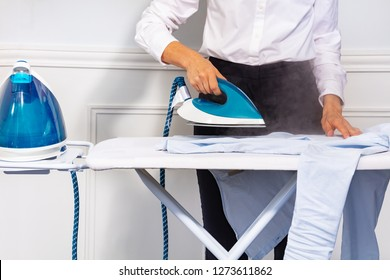 Woman's hand holding steam iron and ironing shirt